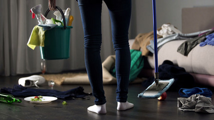 Shocked cleaning lady standing in messy hotel room with mop and washing bucket