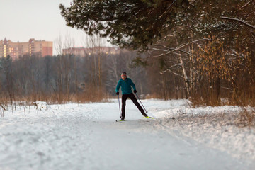 Image of male skier in blue jacket in winter park