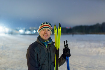 Photo of smiling man with skis in winter forest