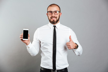 Photo of happy successful man in glasses and tie demonstrating cell phone and showing thumb up, isolated over gray background