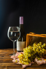 Picture of empty wine glass, grapes of green on wooden basket on table