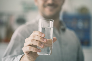 Happy young man holding glass of water inside
