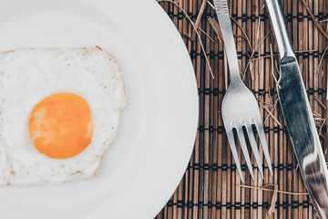 Foto op Canvas Gebakken Eieren Fried egg in white plate and fork on wooden table. Lunch in the cafe.
