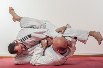 Brazilian jiu-jitsu training demonstration in traditional kimono
