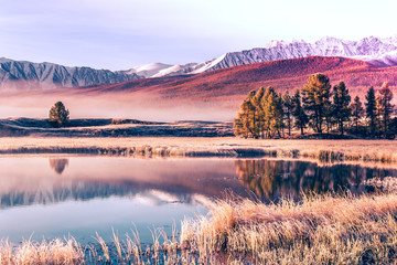 Mirror surface of the lake in the mountain valley. The peaks of the cliffs on the horizon at the colorful sky. Autumn weather