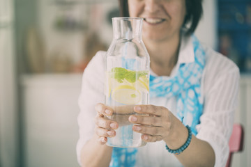 Woman holding  bottle with water lemon and mint in kitchen