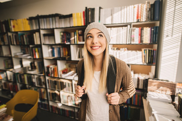 Portrait view of a gorgeous cheerful blond high school student girl standing in the school library.