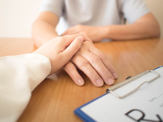Female doctor holding middle-aged patient hands for comforting and  encouragement at hospital. Doctor consulting with her patient about treatment options for the disease and side effects. Health care.