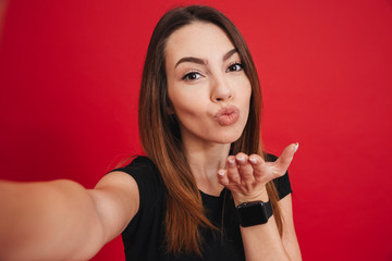 Splendid woman 20s with long brown hair smiling and blowing air kiss on camera, isolated over red background