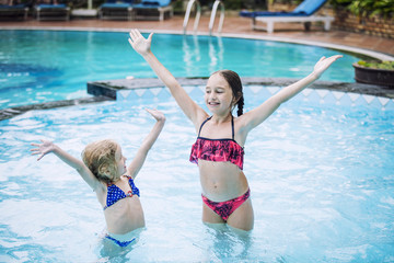 Funny little kids girls smile and swim in the outdoor swimming pool beautiful and happy