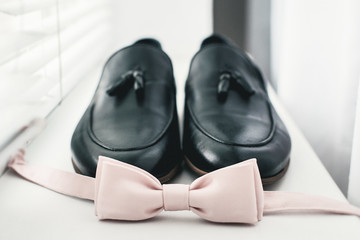Close up of modern man accessories. beige bow tie, black leather shoes