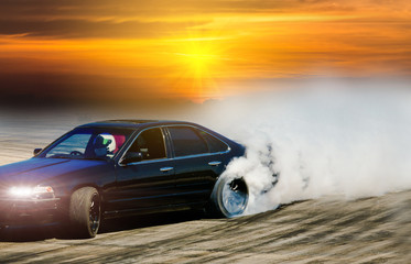 Drift car on race track with smoke from burned tire at sunset.
