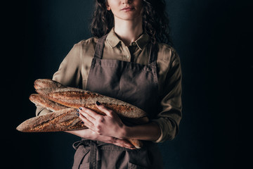 cropped shot of woman in apron holding french baguettes in hands isolated on black