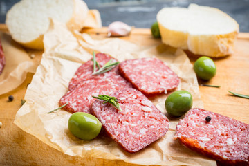 Delicious salami with olives, spices and rosemary. Selective focus.