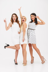 Full length portrait of three cheerful young girls