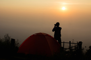 Silhouette tourist shooting picture during sunrise , Relax time on holiday and camping concept ,selective and soft focus,tone of hipster style