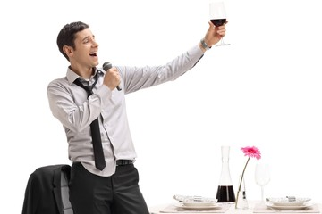 Drunk man holding a glass of wine and singing on a microphone