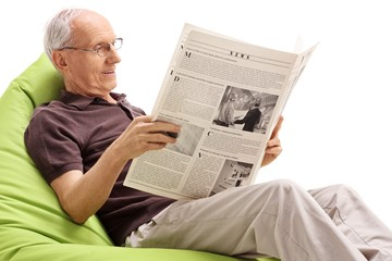 Senior sitting on a beanbag and reading a newspaper