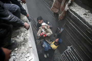 Civil defence help an unconscious woman from a shelter in the besieged town of Douma