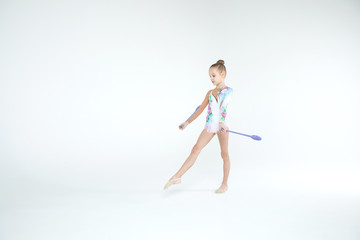 Rhythmic gymnastics caucasian blonde girl in costume for shows performing athlete exercises with gymnastic clubs handling abilities showing flexibility and acrobat balance on white background isolated