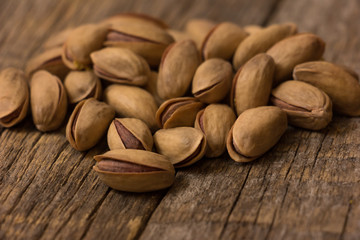 Pistachio Nuts on a wooden background.