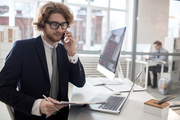 Busy office worker in formalwear talking by phone and reading papers by workplace