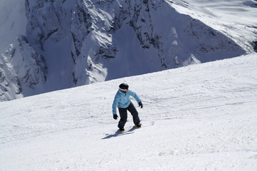 Snowboarder downhill on ski slope in high snowy mountains