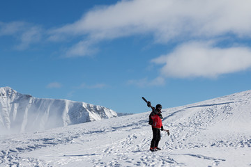 Skier with skis on his shoulder go up to top of mountain