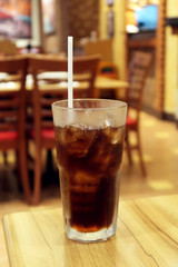 Fresh cola with ice cubes, restaurant background selective focus on glass.