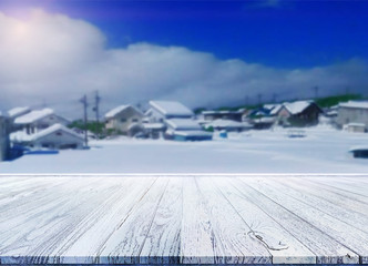Empty brown wooden table top isolated with villages under Japanese snow. Idea for display or put your products.