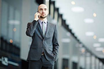 Young elegant businessman in suit speaking by smartphone in airport during travel