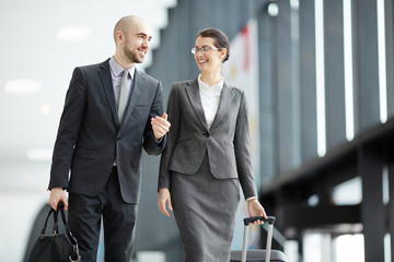 Traveling business partners with liggage having talk while walking along modern airport