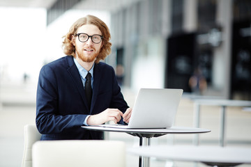 Confident businessman in eyeglasses and elegant suit sitting by table in front of laptop in airport lounge