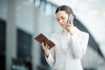 Scowling businesswoman checking information on airplane ticket and talking by smartphone in airport