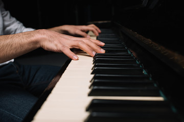 cropped shot of man playing piano on black