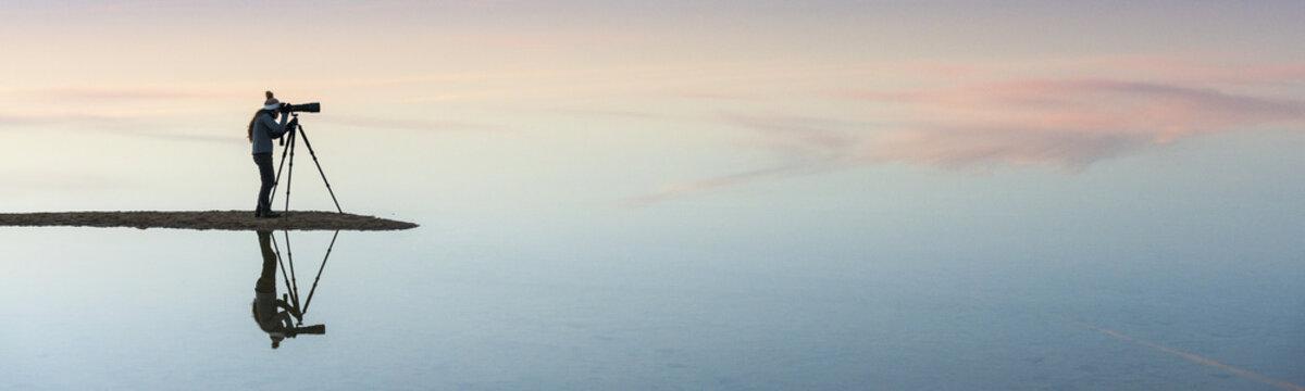 Silhouette and reflection of photographer in Bahariya salt lake