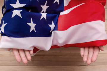 The American flag holds in his hands on a light wooden background. The Flag Of The United States Of America.
