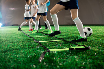 Row of little football players keeping their legs over square cells on green field during training