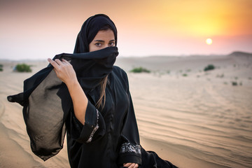Portrait of beautiful young Muslim woman sitting on  sand in the desert during sunset.