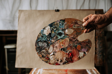 Artist palette with various color in front of a blank paper. Painter palette as artwork.