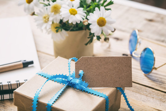 Gift box with blank empty tag, blur office desk background