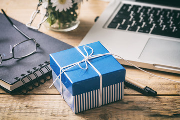 Blue gift box on an office desk, view from above