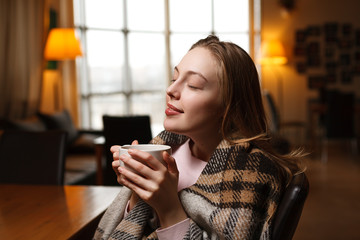 Gorgeous happy woman drinks coffee at a cafe background. Covered cozy plaid. Blurred cafe background.