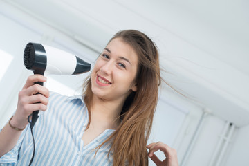 pretty young woman is drying her hair