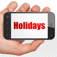 Entertainment, concept: Hand Holding Smartphone with red text Holidays on display, 3D rendering
