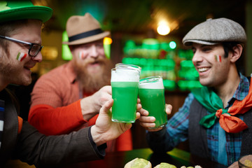 Happy irish football fans clinking with glasses of green foaming beer in pub
