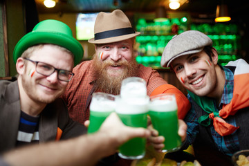 Happy friends toasting with glasses of foaming beer while gathering in pub