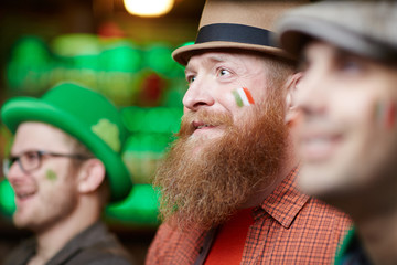 Bearded irish football fan and his friends watching match broadcast in pub
