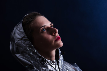 Portrait of young cosmic woman wearing in shiny hood look at the sky. Retro futurism concept.