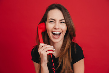 Photo of pretty brunette woman in black casual talking and laughing at retro handset, over red background